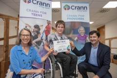 Cian Horgan smiles with his certificate of achievement  beside founder Kate Jarvey and Tomar Trust's Cal Healy