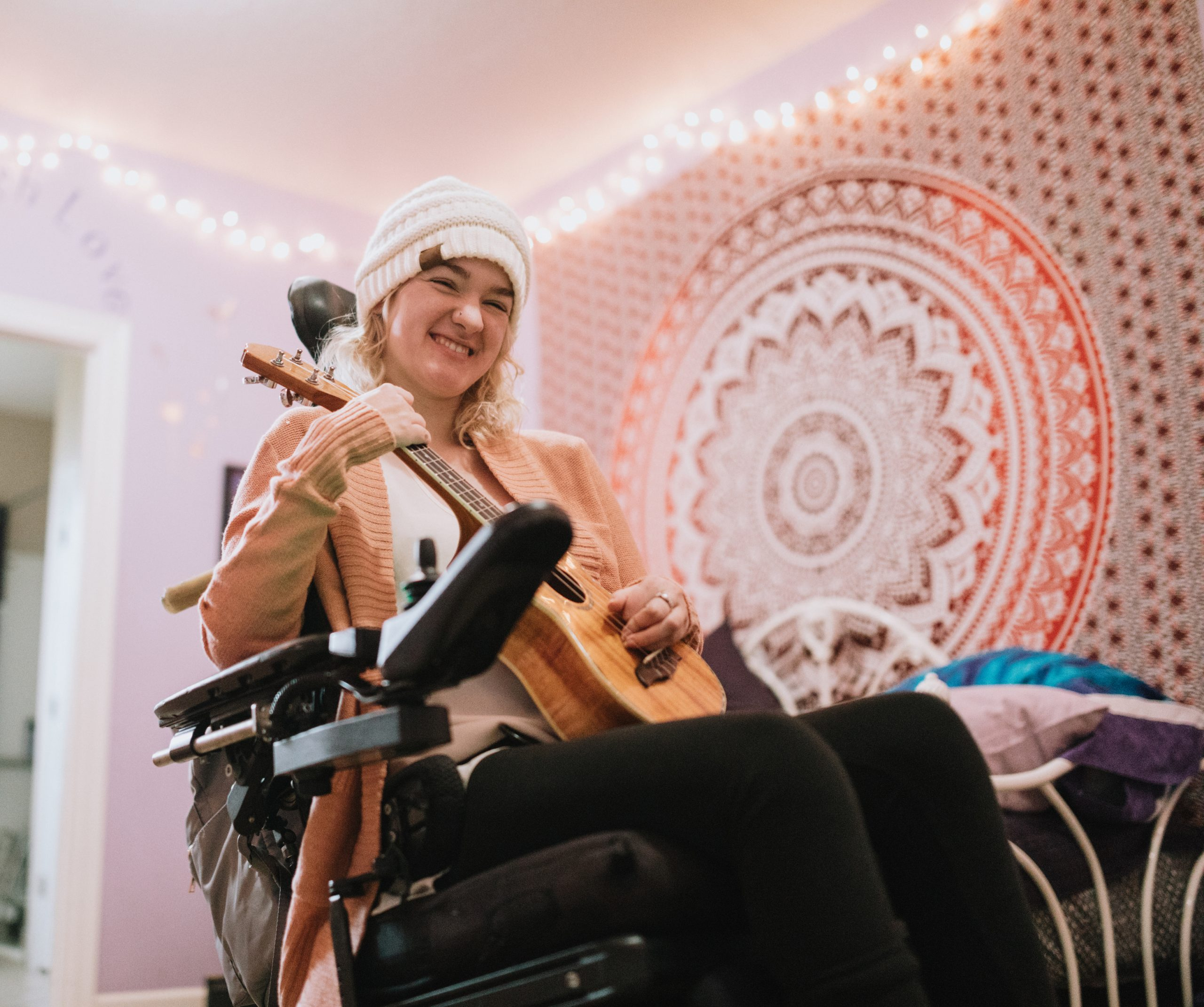 Cheerful Young Woman In Wheelchair At Home With Ukulele