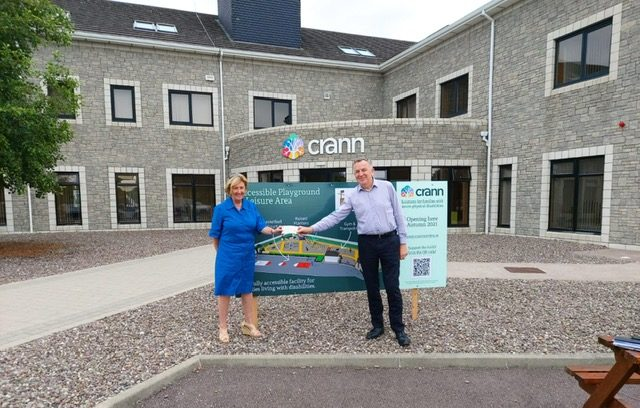 CEO of MCS Case Management, Siobhan McSweeney presenting a cheque to Crann CEO Padraig Mallon outside the Crann building.